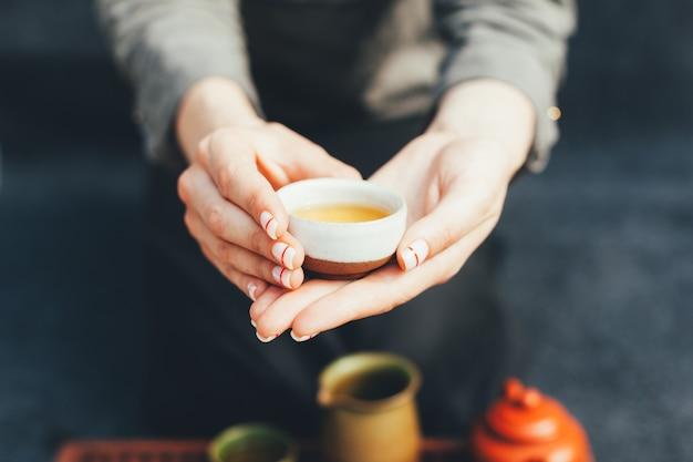 Vrouw biedt hete thee aan in een vintage keramische beker