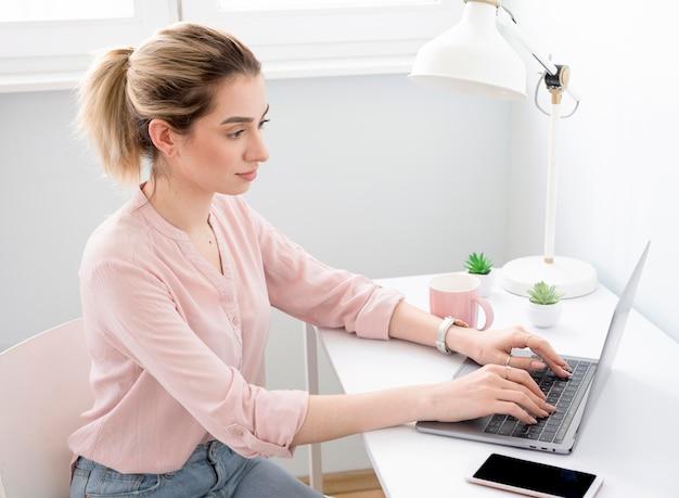 Vrouw bij bureau dat van huis werkt