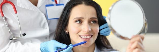 Vrouw bij de afspraak van de schoonheidsspecialiste kijkt in de spiegel. verjongend concept voor gezichtsbehandelingen