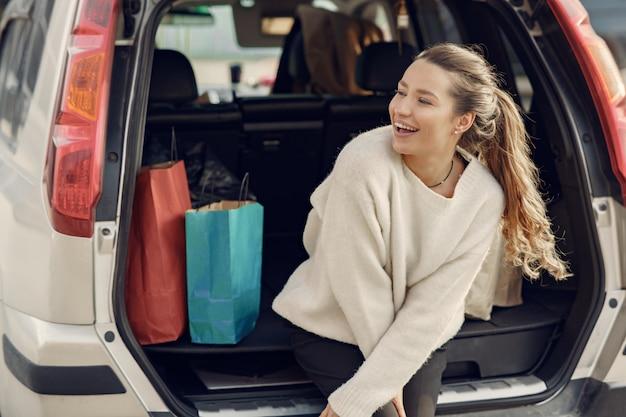 Vrouw bij de auto met een boodschappentassen