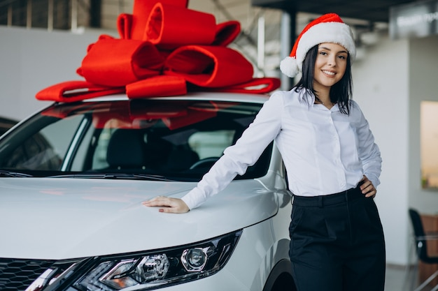 Vrouw bij de auto met rode strik