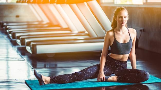 Vrouw bij de gymnastiek die uitrekkende oefeningen doet en op de vloer glimlacht