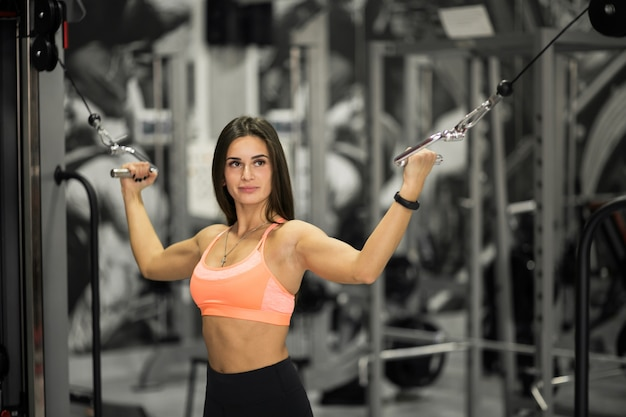 Vrouw bij de gymnastieklichaamsbouw