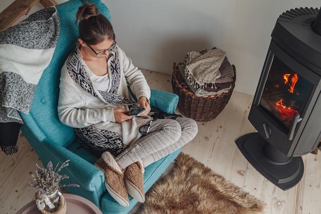 Vrouw bij de open haard, zittend in een gezellige fauteuil met warme kleding en met behulp van mobiele telefoon