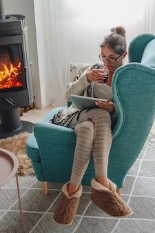 Vrouw bij de open haard, zittend in een gezellige fauteuil met warme kleding en met behulp van tablet