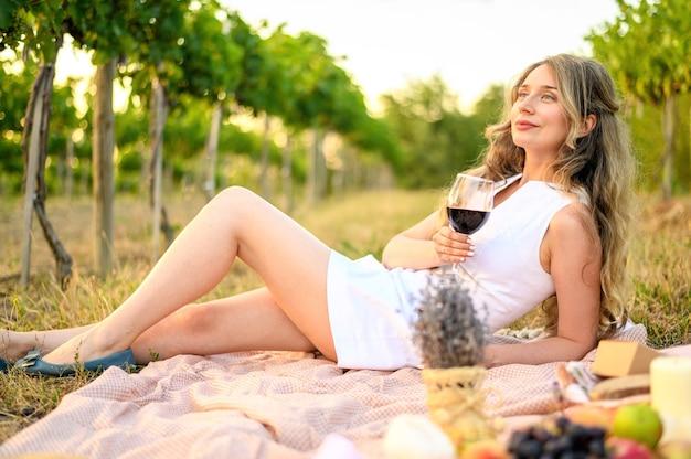 Vrouw bij de picknick met een glas wijn. vine yard groene achtergronden