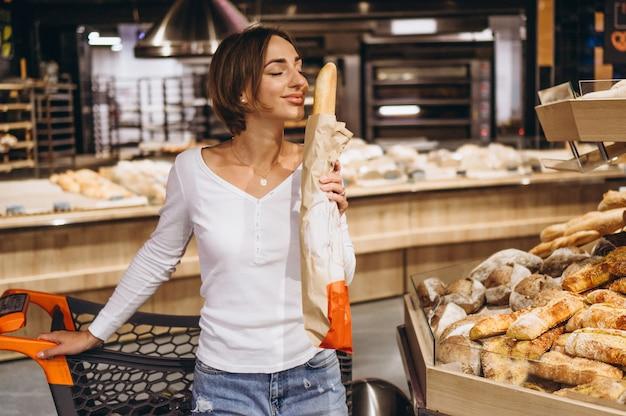 Vrouw bij de supermarkt die vers brood koopt