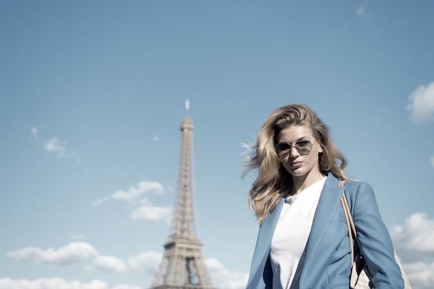 Vrouw bij de toren van eiffel in parijs, frankrijk op blauwe hemel. meisje reiziger in zonnebril, jas op zonnige zomerdag buiten. architectuur, attractie, mijlpaal. vakantie, reizen, reislust, frankrijk