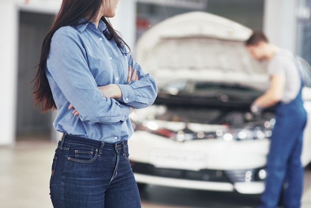 Vrouw bij een autogarage die de mechanische dienst krijgt. de monteur werkt onder de motorkap van de auto