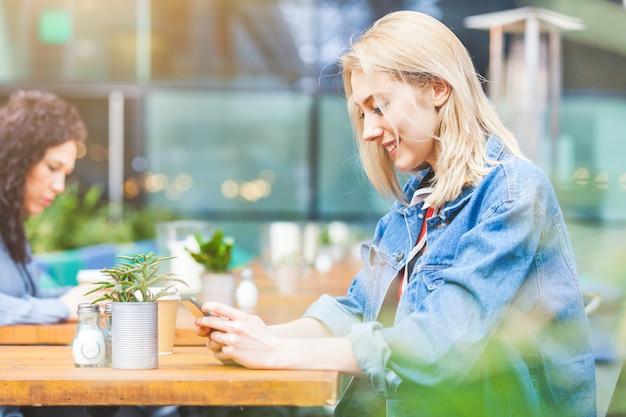 Vrouw bij een koffie die haar slimme telefoon bekijkt