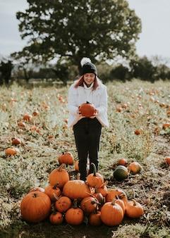 Vrouw bij een pompoenveld voor halloween