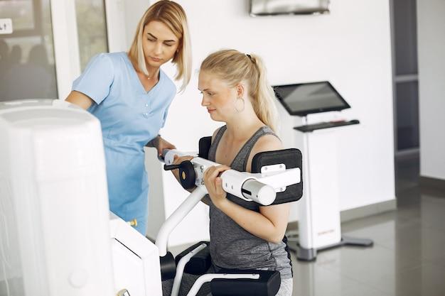 Vrouw bij fysiotherapie fysieke oefeningen met gekwalificeerde therapeut maken