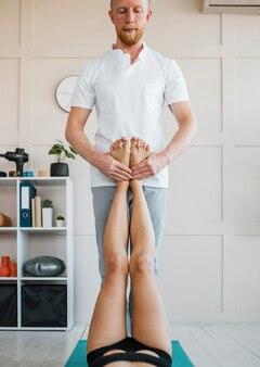 Vrouw bij fysiotherapie met mannelijke fysiotherapeut