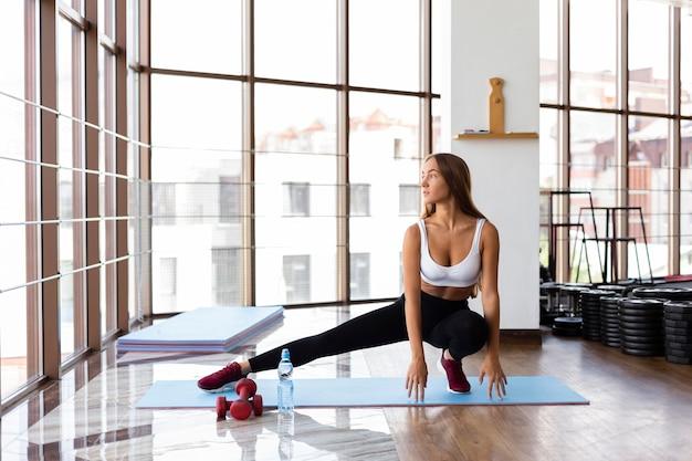Vrouw bij gymnastiek bij zich het uitrekken van de mat