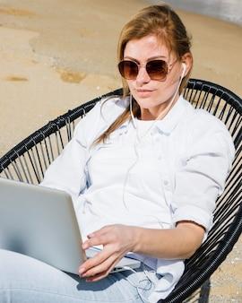 Vrouw bij het strand dat aan laptop werkt