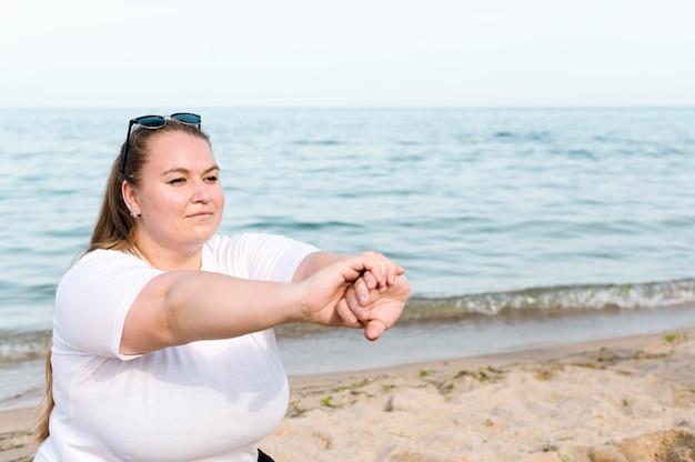 Vrouw bij het strand dat sportoefeningen doet
