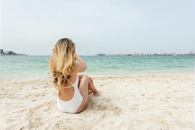Vrouw bij het strand dat van doubai witte zwempakken draagt