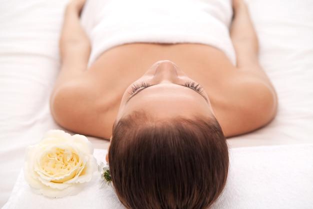 Vrouw bij kuuroord. bovenaanzicht van mooie jonge vrouw liggend op massagetafel