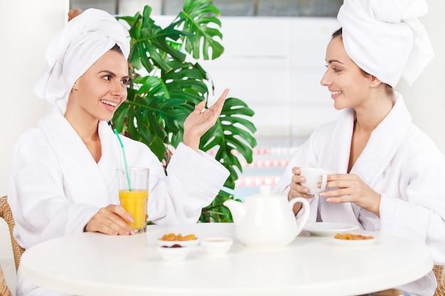 Vrouw bij kuuroord. twee mooie jonge vrouwen in badjas die sap drinken en met elkaar praten terwijl ze voor het zwembad zitten