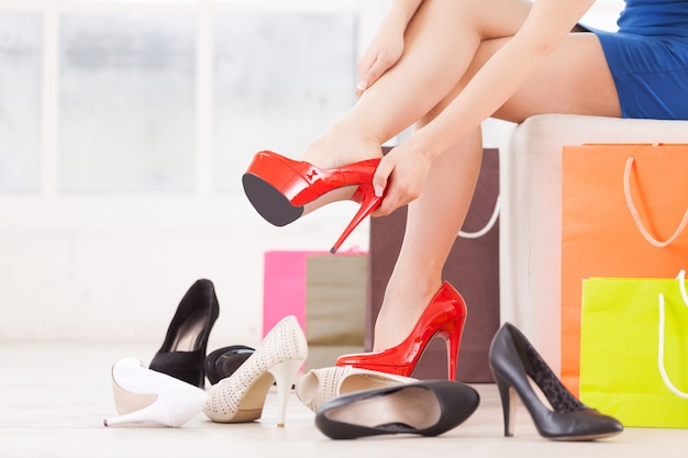 Vrouw bij schoenenwinkel. bijgesneden afbeelding van jonge vrouw die schoenen kiest in een schoenenwinkel