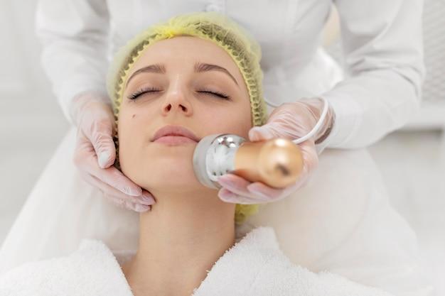 Vrouw bij schoonheidskliniek voor gezichtsbehandeling