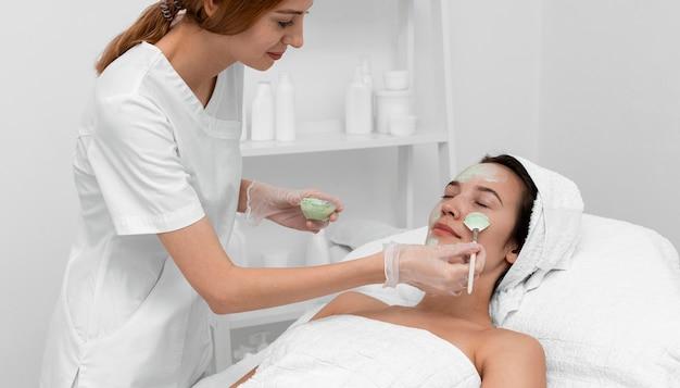 Vrouw bij schoonheidssalon voor gezichtsbehandeling