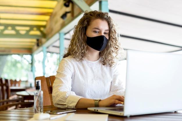 Vrouw bij terras met masker met behulp van laptop