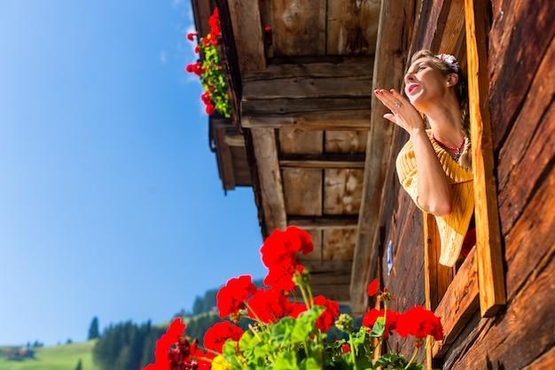 Vrouw bij venster van berghut in alpen