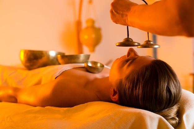 Vrouw bij wellness-massage met klankschalen