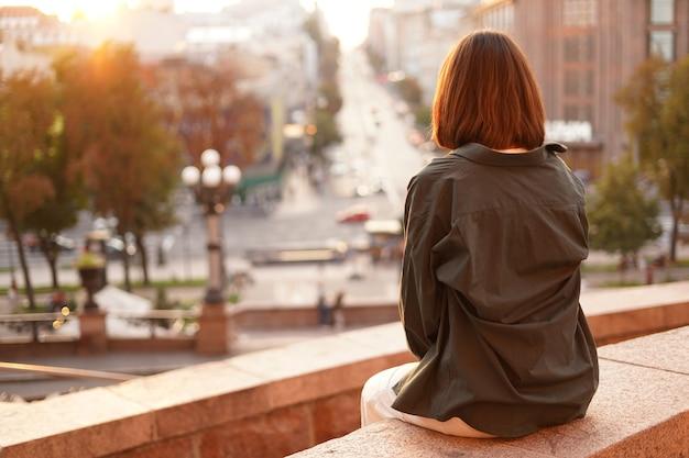 Vrouw bij zonsondergang met geweldig uitzicht op de stad, genietend van warme dagen, vrijheid, positieve vibes