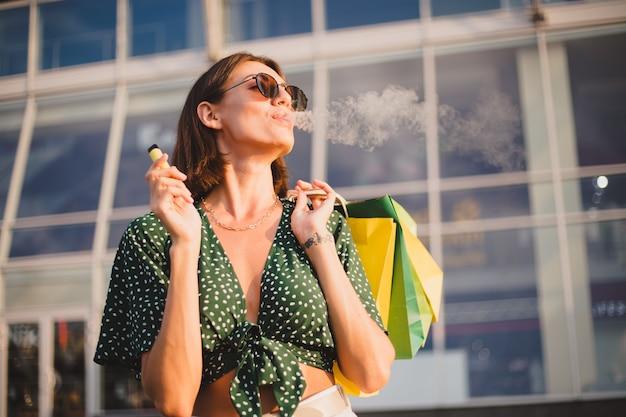 Vrouw bij zonsondergang met kleurrijke boodschappentassen en koffie roken genieten van elektronische sigaret