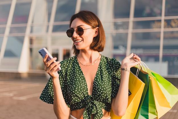 Vrouw bij zonsondergang met kleurrijke boodschappentassen en parkeerplaats bij winkelcentrum blij met mobiele telefoon