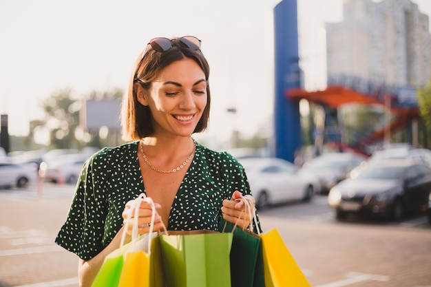 Vrouw bij zonsondergang met kleurrijke boodschappentassen en parkeerplaats bij winkelcentrum blij vrolijk na winkeldag
