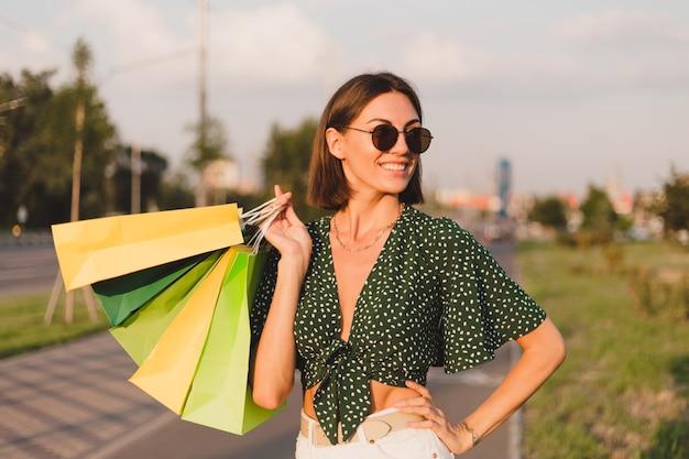 Vrouw bij zonsondergang met kleurrijke boodschappentassen in het stadsstraatpark na de winkeldag happy
