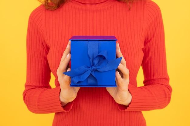 Vrouw bijgesneden weergave houdt blauwe geschenkdoos met lint boog decoratie vakantie viering gele achtergrond, aanwezig.