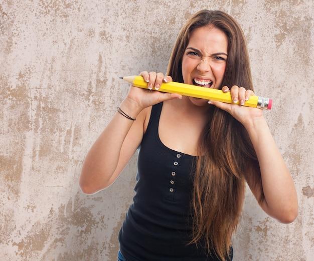 Vrouw bijt een groot potlood