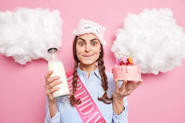 Vrouw bijt lippen en kijkt met verleiding heeft verlangen om heerlijke verjaardagstaart met melk te eten geniet van het vieren van verjaardag in huiselijke sfeer poses binnen. vakantie concept