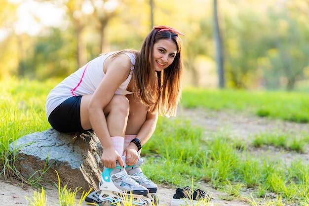 Vrouw bindt haar inline skates vast terwijl ze in een park zit en naar de camera kijkt