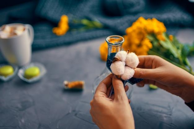 Vrouw bindt het katoen aan de vaas