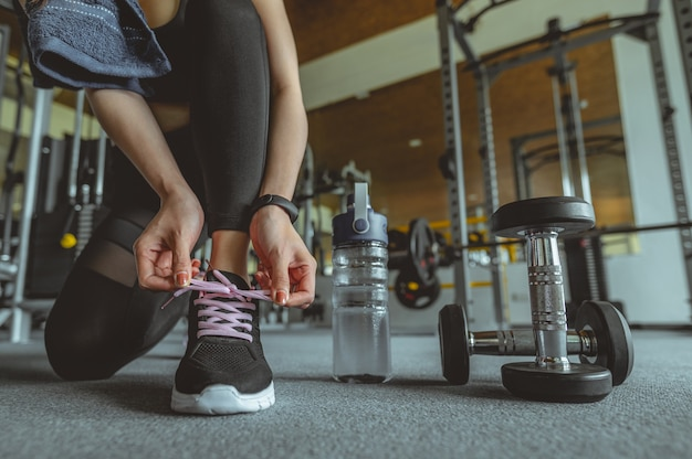 Vrouw bindt schoenveters bij gym jonge vrouw bij gym neemt een pauze van training fitness workout gym