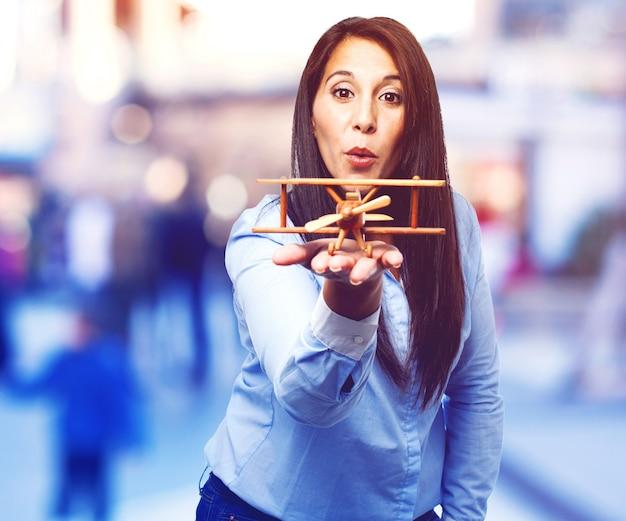 Vrouw blaast een houten vliegtuig