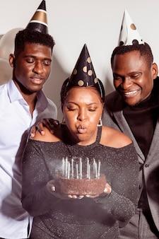 Vrouw blaast kaarsen gelukkige verjaardag