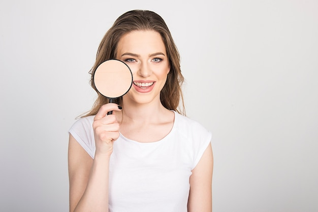 Vrouw blij met haar schone, gezonde huid schoonheid huidverzorging concept. vrouw met vergrootglas op haar gezicht met schone huid.