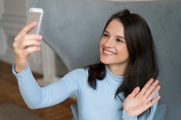 Vrouw blijft in bed terwijl ze een videogesprek voert op haar smartphone