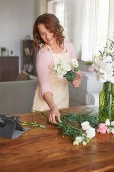 Vrouw bloemen arrangement maken