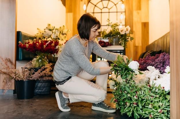 Vrouw bloemist bloemen plukken voor een boeket in bloemenwinkel