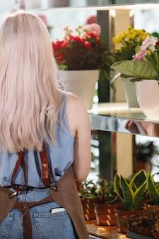 Vrouw bloemist in een werkschort tegen een achtergrond van bloemen en boeketten. selectieve aandacht. achteraanzicht.