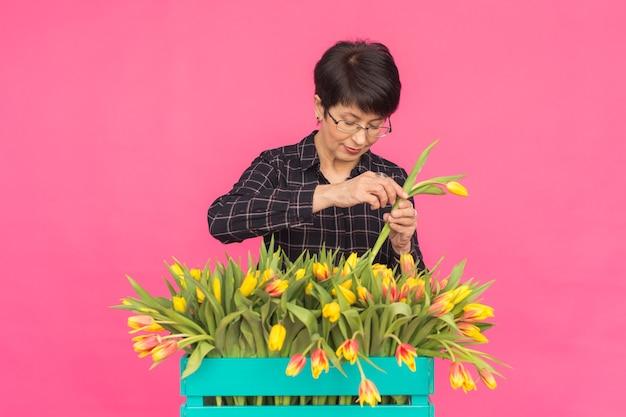 Vrouw bloemist op middelbare leeftijd met houten doos tulpen op roze muur