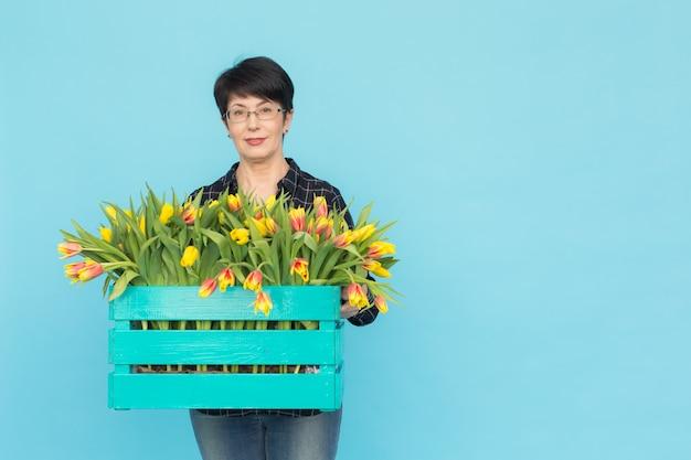 Vrouw bloemist van middelbare leeftijd met houten doos tulpen op blauwe achtergrond met kopie ruimte