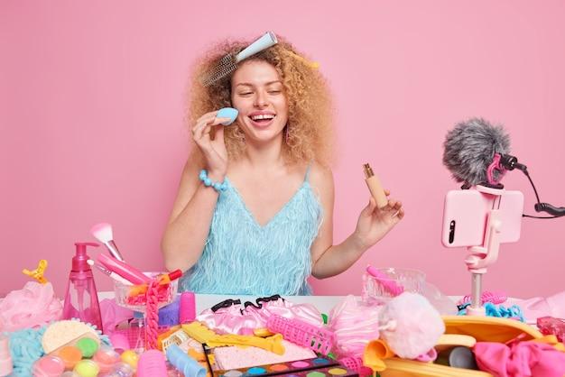 Vrouw blogger brengt foundation op gezicht aan heeft kam in haar zit draagt blauwe jurk zit aan tafel met schoonheidsproducten in de buurt gebruikt mobiele telefoon om video op te nemen blog